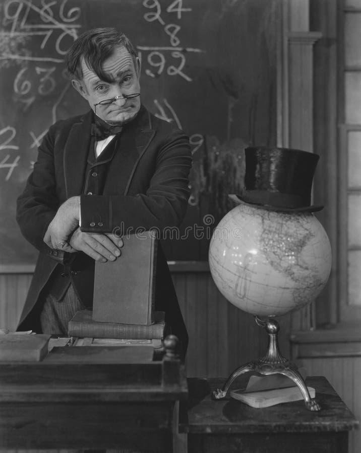 Math teacher uses globe as hat stand stock photo