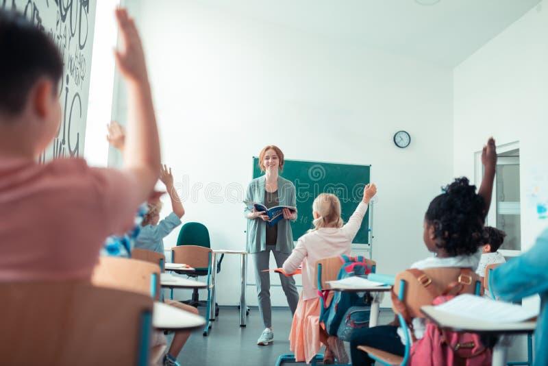 Mathelehrer, der zu ihrer Klasse an der Lektion lächelt lizenzfreie stockfotos