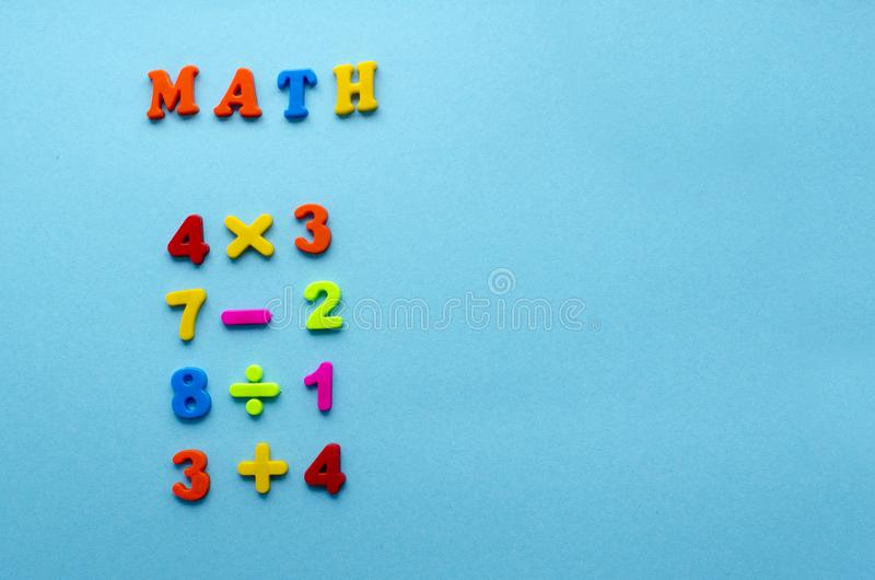 Mathematical actions on blue paper background.  stock image