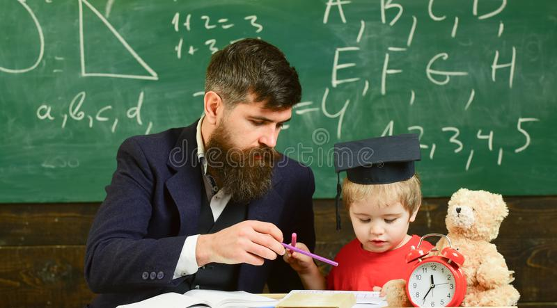 Mathematics lesson concept. Father teaches son mathematics. Teacher in formal wear and pupil in mortarboard in classroom royalty free stock photos