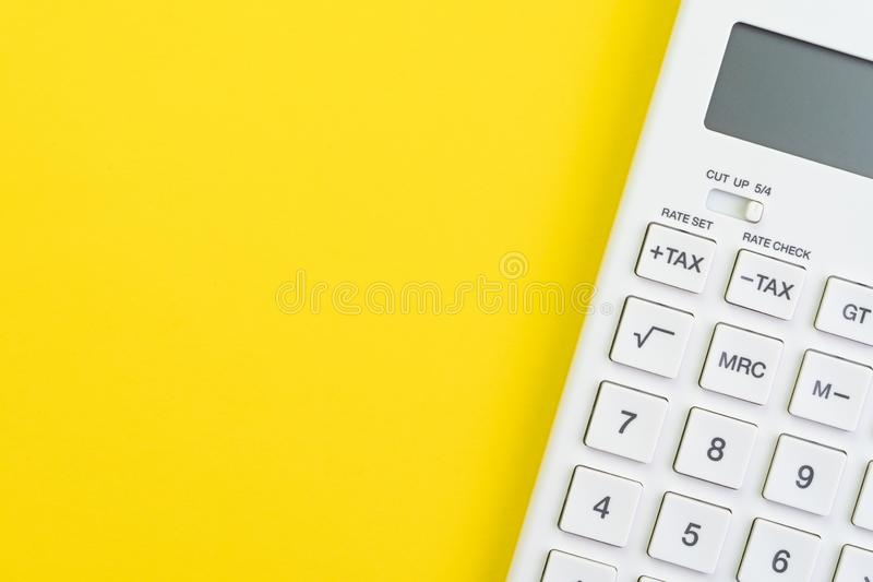 Mathematics, tax calculation, finance or investment concept, white clean calculator on solid yellow background with copy space.  royalty free stock image