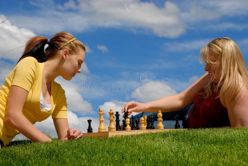 Mather and daughter playing chess stock images