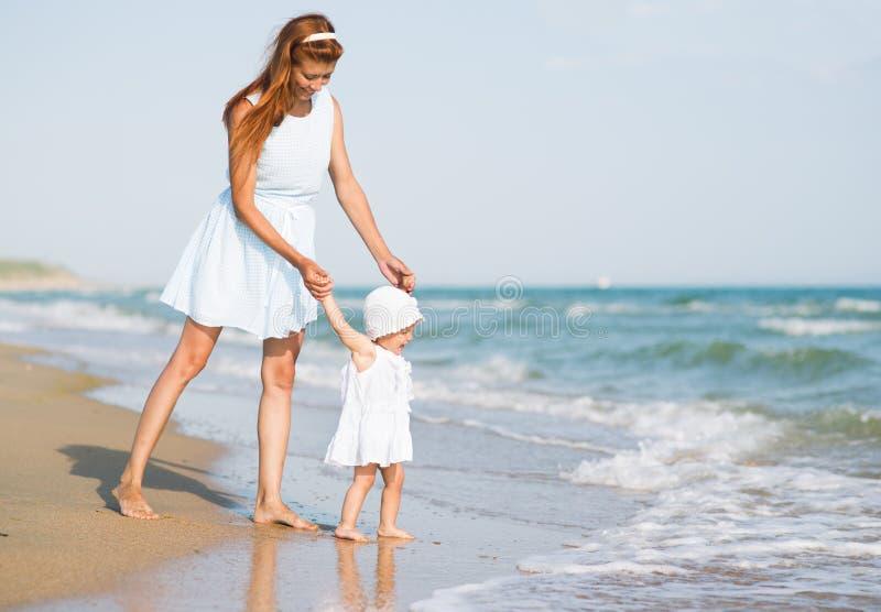 Mather e bambino sulla spiaggia dell'oceano fotografia stock libera da diritti