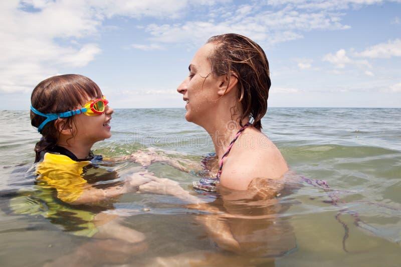 Mather e filha que jogam no mar fotografia de stock royalty free