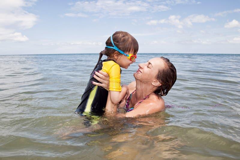 Mather e filha que jogam no mar imagem de stock