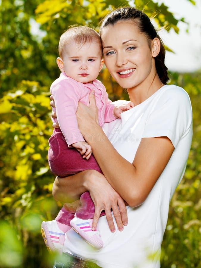 Mather feliz con el bebé atractivo al aire libre fotos de archivo libres de regalías