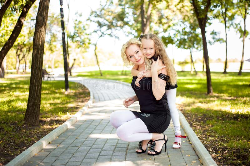 Mather and her daughter in the park. Mather and her daughter in the park stock images