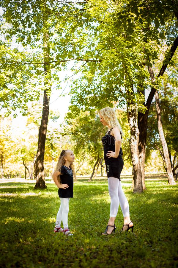 Mather and her daughter in the park. Mather and her daughter in the park stock photos