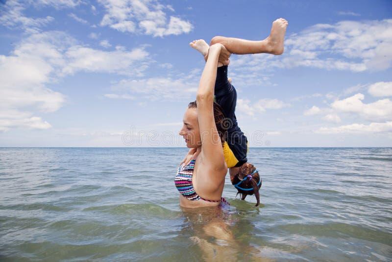 Mather och dotter som spelar i havet royaltyfria bilder