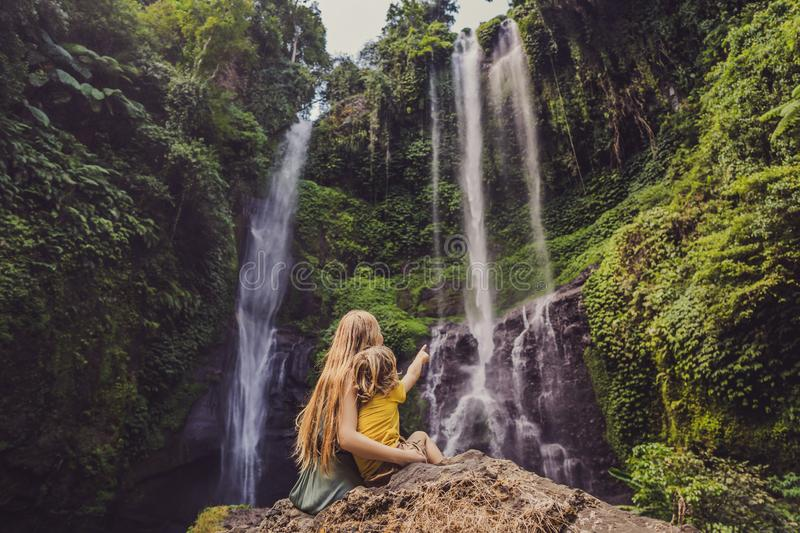 Mather and son at the Sekumpul waterfalls in jungles on Bali island, Indonesia. Bali Travel Concept.  royalty free stock photo