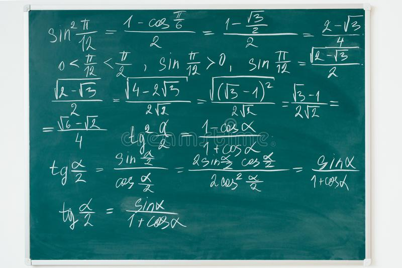 Maths formulas written by white chalk on the blackboard. stock photos