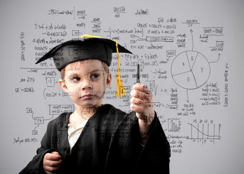 Maths genius. Child in graduate uniform doing some maths exercises royalty free stock images