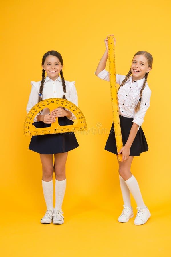 Maths heureuses disciplines de tige De nouveau ? l'?cole Maths et géométrie Enfants dans l'uniforme au mur jaune Amiti? et photo libre de droits