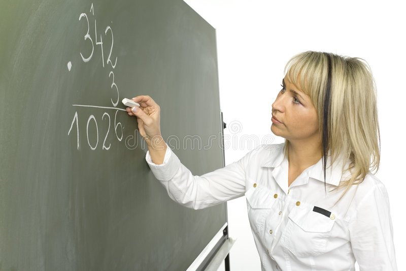 Maths lesson. Mid age woman (teachear) are standing with chalk in hand close to greenboard. She's doing maths stock photos