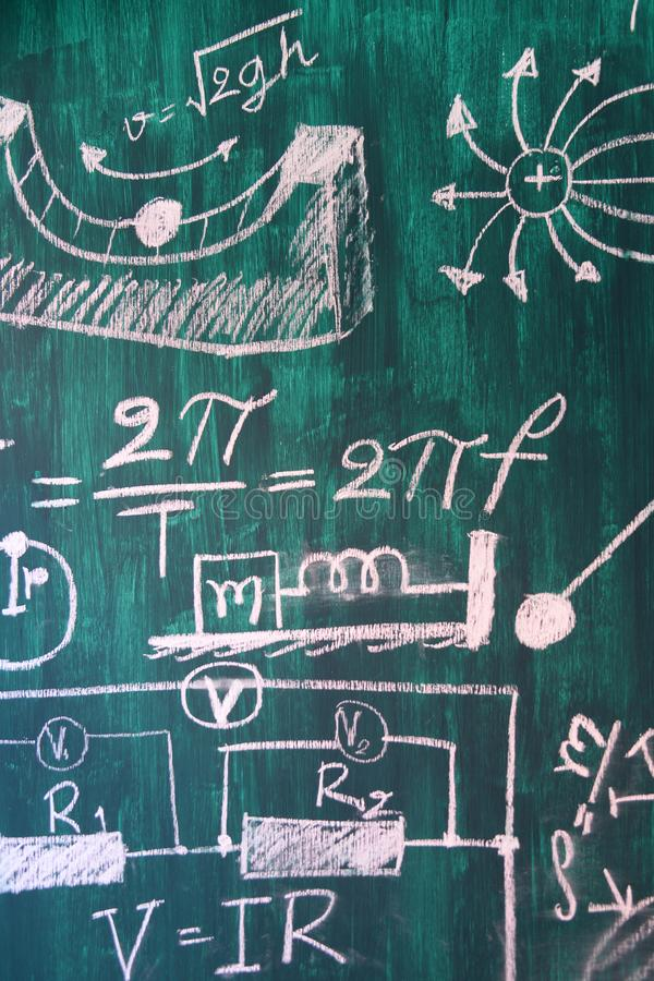 Maths and physic formulas written by white chalk on the blackboard background stock image