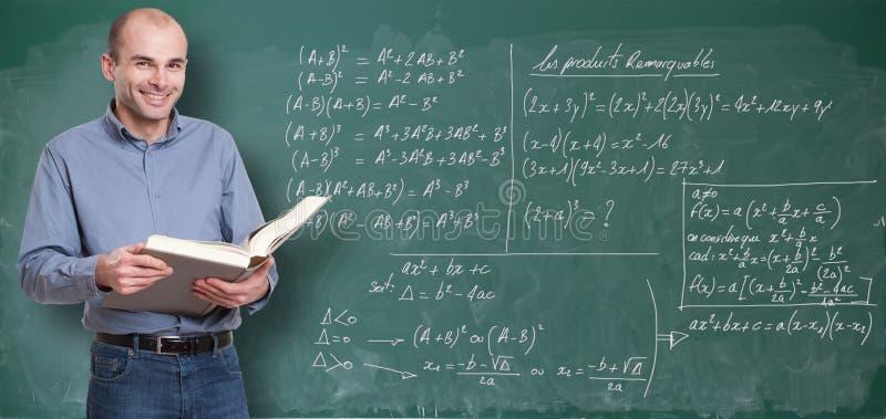 Maths teacher. Friendly maths teacher by the blackboard stock image