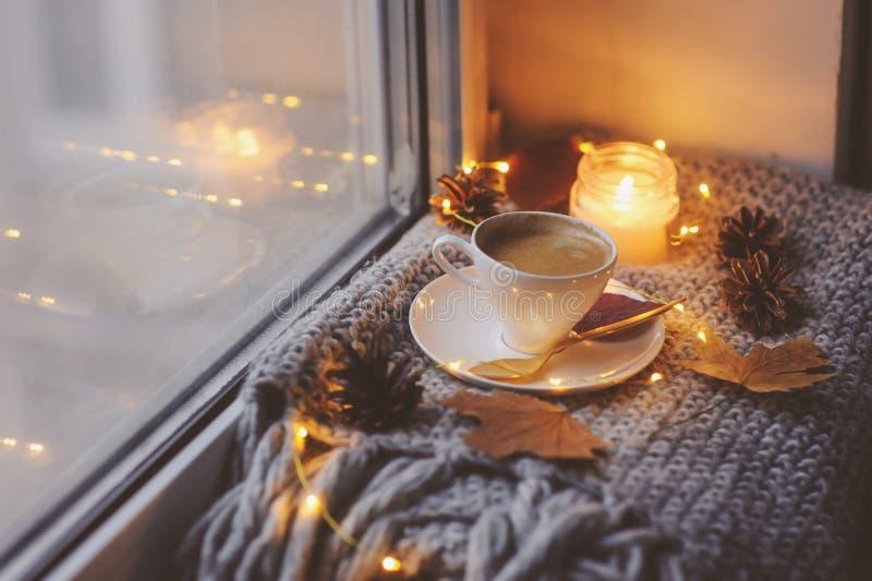 Matin confortable d'hiver ou d'automne à la maison Café chaud avec la cuillère métallique d'or, les lumières chaudes de couvertur photos stock