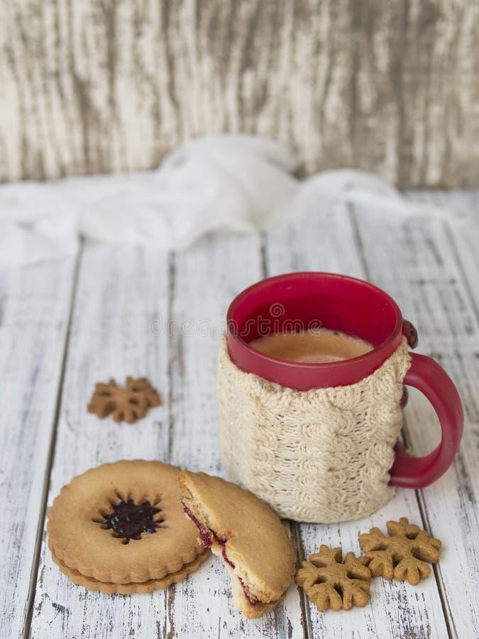 Matin d'hiver, tasse de café avec les supports de tasse tricotés, pain d'épice et biscuits de vanille sur un fond en bois blanc photographie stock