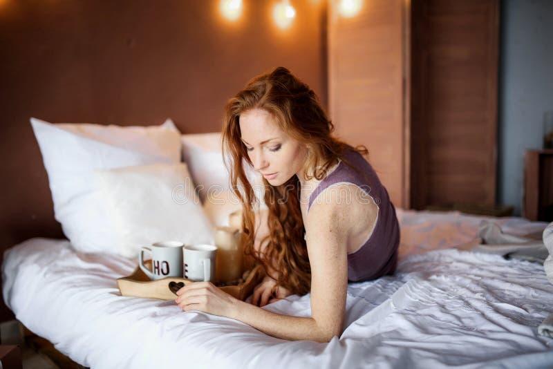 Matin dans le lit, une jeune femme rousse avec du charme avec des taches de rousseur se situant dans le lit, ?treignant l'oreille photographie stock