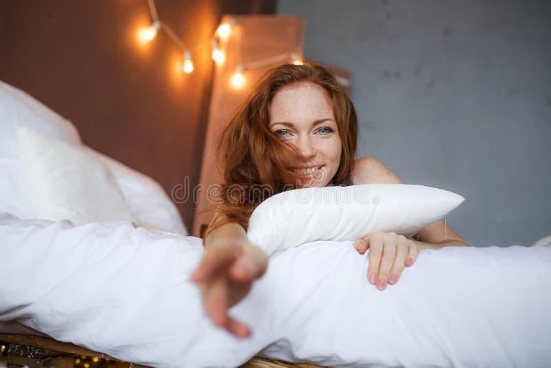 Matin dans le lit, une jeune femme rousse avec du charme avec des taches de rousseur se situant dans le lit, ?treignant l'oreille image libre de droits