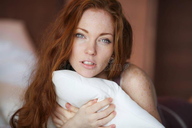 Matin dans le lit, une jeune femme rousse avec du charme avec des taches de rousseur se situant dans le lit, ?treignant l'oreille photographie stock libre de droits