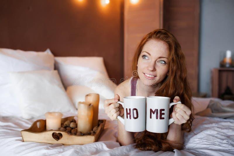 Matin dans le lit, une jeune femme rousse avec du charme avec des taches de rousseur se situant dans le lit, ?treignant l'oreille photo libre de droits