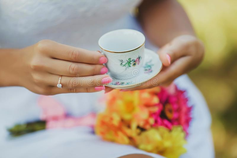 Matin de la jeune mariée, café pour le petit déjeuner, robe blanche et mains sensibles, main du ` s de femme élégante avec la bel images libres de droits