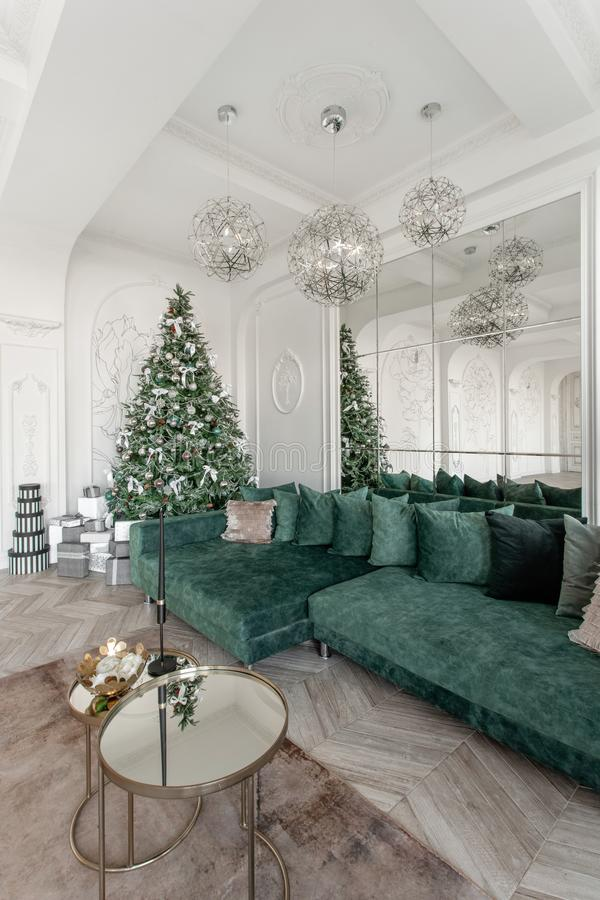 Matin de Noël appartements luxueux classiques avec l'arbre de Noël décoré Grand miroir vivant de hall, sofa vert images stock