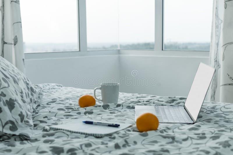 Matin en appartement moderne - un ordinateur portable ouvert sur le lit près de la fenêtre, à côté de la tasse de café image stock