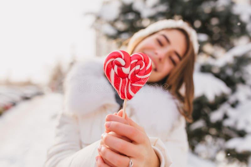 Matin ensoleillé heureux d'hiver de lollypop joyeux de coeur de rose de plan rapproché de participation de fille sur la rue Temps photo libre de droits