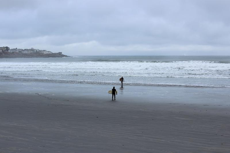 Matin froid à la plage, avec deux surfers rendant prêts à monter des vagues, York, Maine, 2018 photos stock