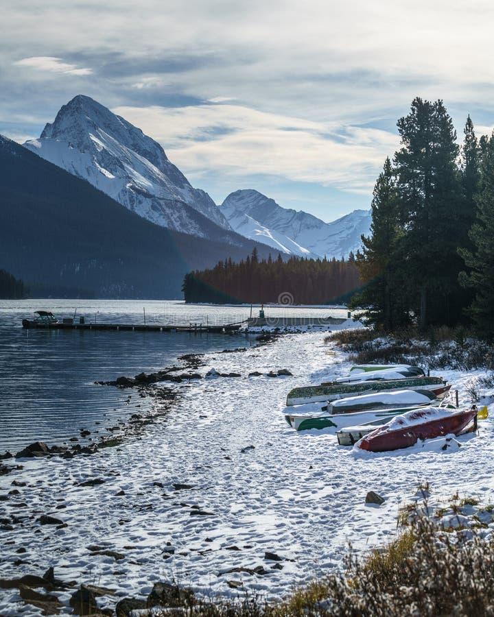 Matin froid avec la neige couvrant des canoës dans le lac de maligne, Alberta, Canada image stock