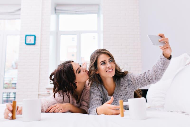 Matin heureux de deux filles attirantes joyeuses faisant le selfie sur le lit blanc Assez jeunes femmes ayant l'amusement ensembl photos stock