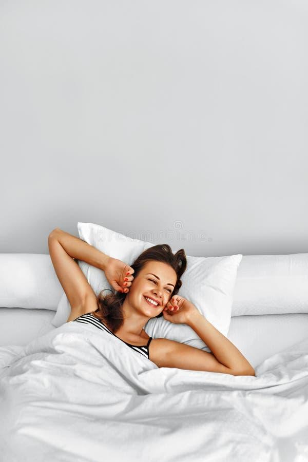 Matin La femme en bonne santé après réveillent la détente dans le lit santé photos libres de droits