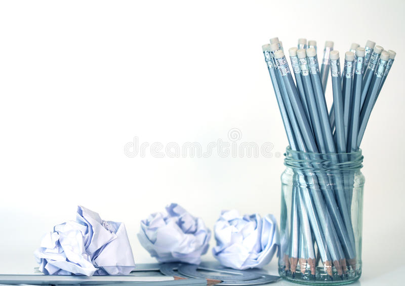 matita d'argento in barattolo di vetro con la carta sgualcita sulla parte posteriore di bianco fotografie stock libere da diritti