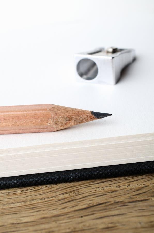 Matita ed affilatrice alla pagina in bianco dello Sketchbook immagini stock libere da diritti