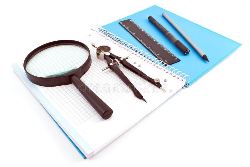 Matita, penna, bussola di disegno, lente e righello di legno sullo spira immagini stock libere da diritti