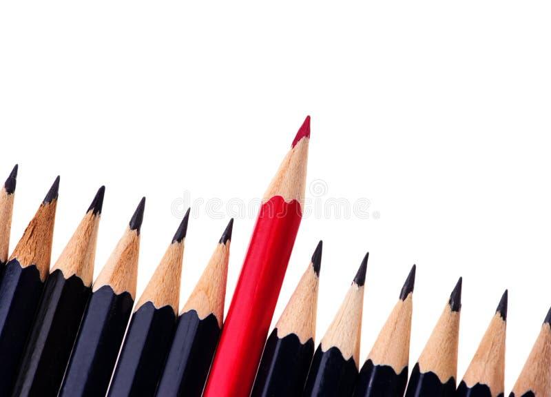 Matita rossa che sta fuori dalla folla dei colleghi neri identici di abbondanza su fondo bianco Concetto di successo di affari immagine stock libera da diritti