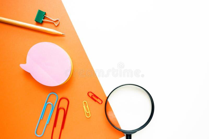 Matita semplice, graffette, lente, cancelleria dell'ufficio sotto forma di disposizione sopra un doppio fondo di bianco e di aran fotografia stock
