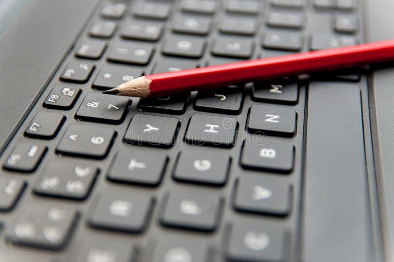 Matita tagliente rossa sulla tastiera del computer portatile fotografie stock
