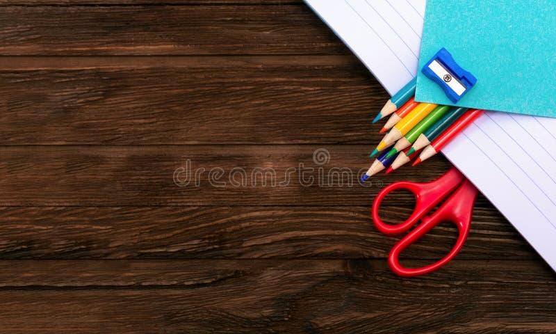 Matite, affilatrice, forbici e strati colorati per le note in un taccuino aperto su una superficie di legno marrone scura Disposi fotografia stock libera da diritti