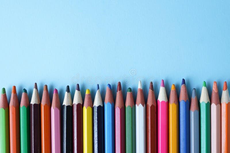 Matite colorate su fondo blu, spazio della copia Di nuovo al concetto del banco Disposizione piana, vista superiore immagini stock libere da diritti