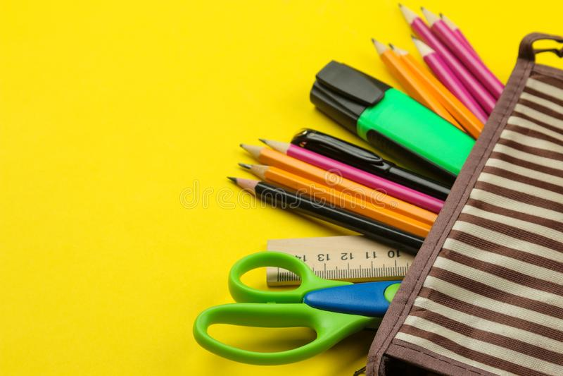 Matite di colore in un astuccio per le matite della scuola su un fondo giallo di carta luminoso Strumenti dell'ufficio Istruzione immagini stock libere da diritti