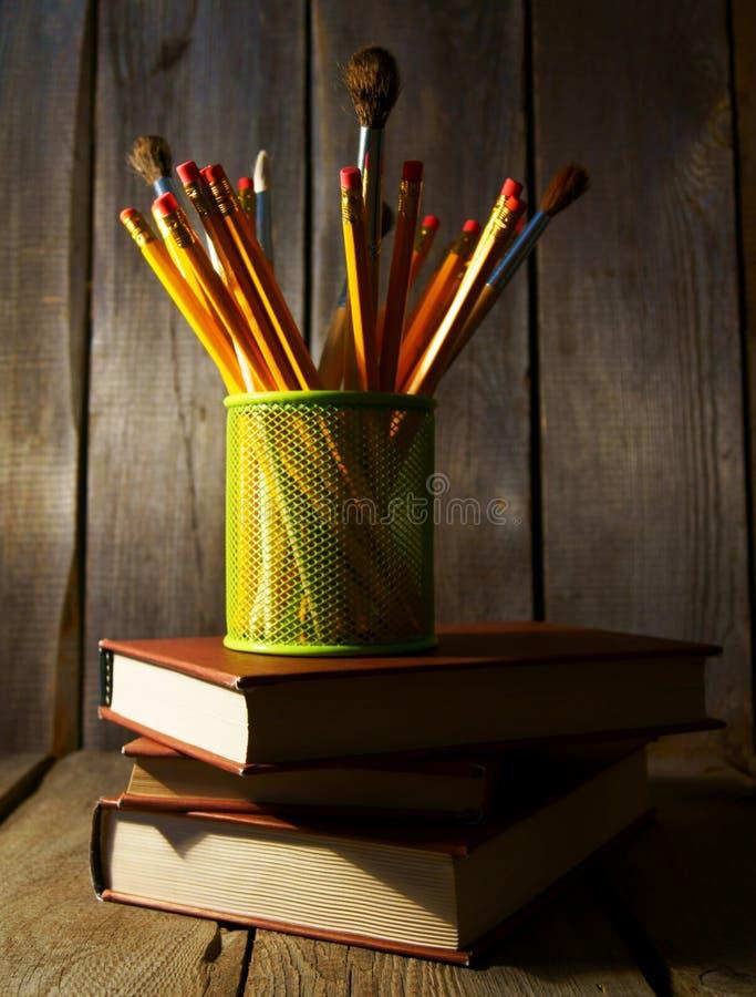 Matite e libri Su fondo di legno immagine stock libera da diritti