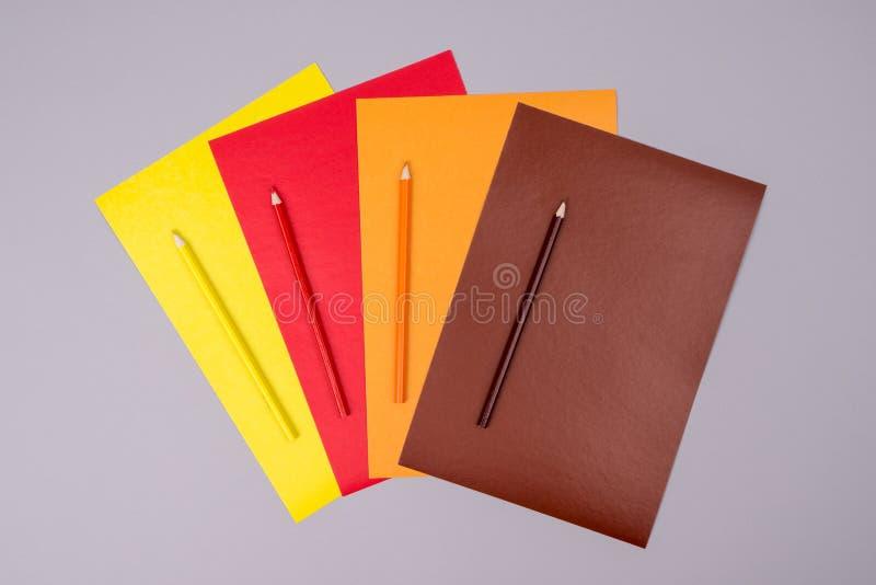 Matite gialle, rosse, arancio e marroni con carta colorata su un fondo grigio immagini stock