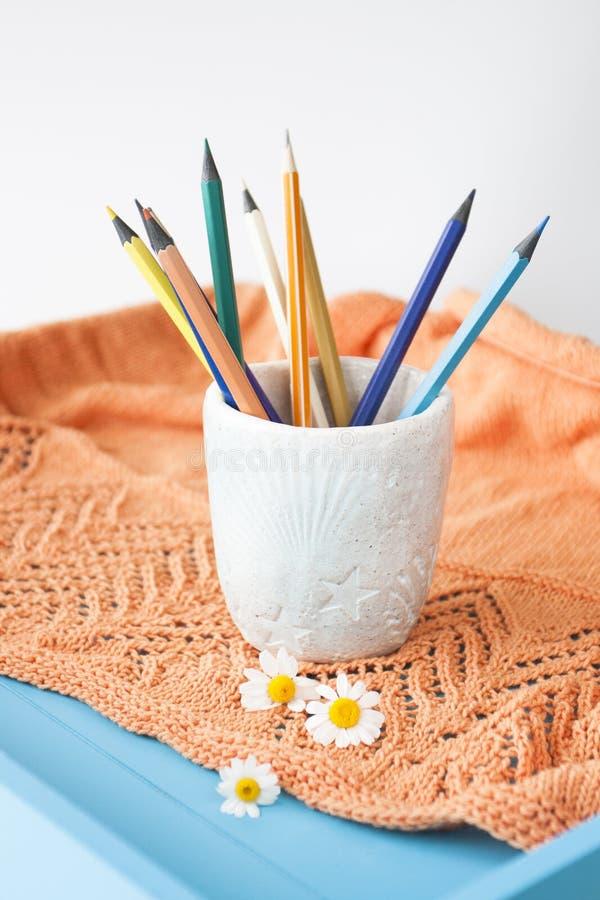 Matite luminose di legno, plaid arancio, tre fiori della camomilla immagini stock