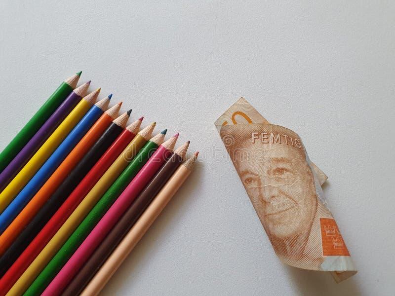 matite svedesi di colore e dei soldi sui precedenti bianchi fotografia stock libera da diritti