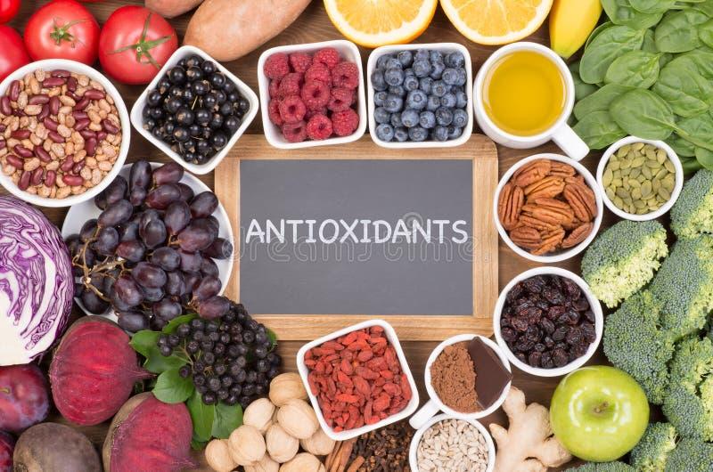 Matkällor av naturliga antioxidants liksom frukter, grönsaker, muttrar och kakaopulver royaltyfri fotografi