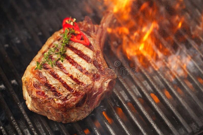 Matkött - nötköttbiff på bbq-grillfestgaller med flamman royaltyfria bilder