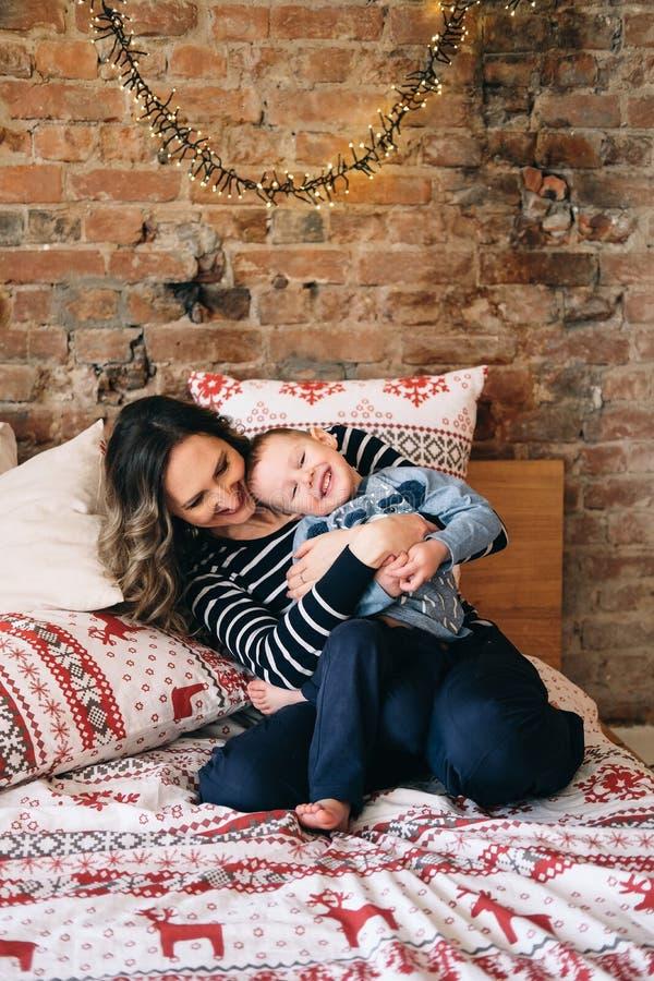 Matka łaskocze jej syna, szczęśliwa rodzina zabawę przy łóżkiem na żywym pokoju fotografia royalty free